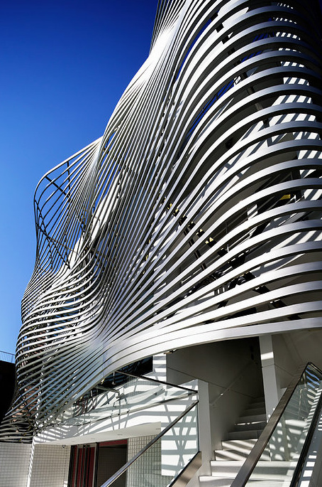 An Undulating Facade Of Metallic Louvers Defines This