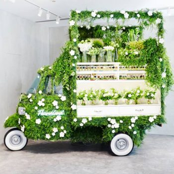 A Piaggio Ape Covered in Green and Converted Into a Flower Shop
